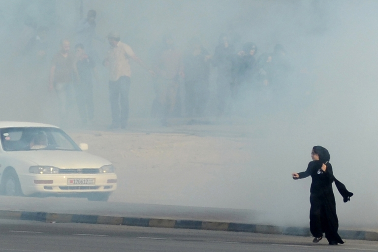 <p>In this photo from December 23, 2011, Bahraini anti-government protesters run for cover from tear gas during clashes with riot police near the headquarters of the main Shiite opposition group, Al-Wefaq, in Zinj Village, west of Manama. A rights group is reporting that six Americans have been arrested amid protests marking the one-year anniversary of the Shiite uprising in Bahrain. AFP PHOTO/STR</p>