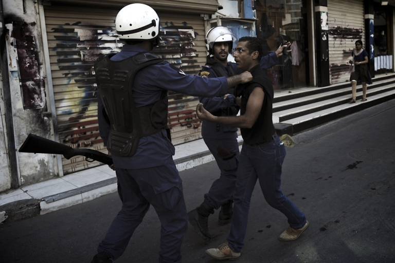 <p>A Bahraini Shiite protester is detained by riot police during an anti-government demonstration in the centre of the capital Manama on September 21, 2012.</p>