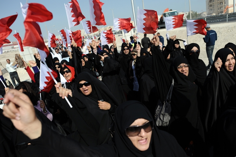 <p>Bahraini women wave their national flag during a rally of Shiite employees who were dismissed from their jobs over pro-democracy protests, near the ministry of labour in Isa Town, south of the capital Manama, on December 27, 2011. Demonstrations have been rekindled in the days leading up to the first anniversary of Bahrain's Shiite uprising on February 14, 2011. AFP PHOTO/STR</p>