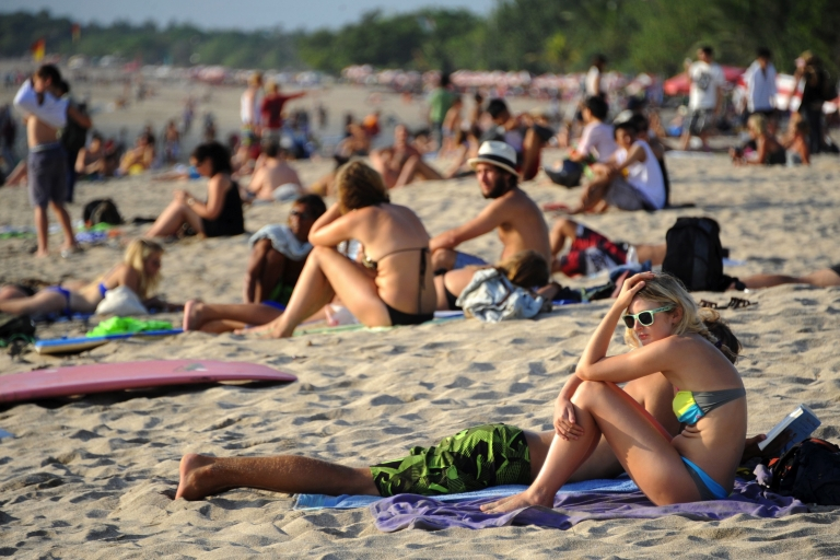 <p>Tourists enjoy Kuta beach on the Indonesian resort island of Bali on October 10, 2011, among tens of thousands who visitor each year.</p>