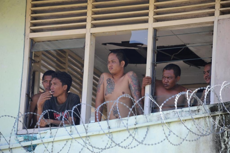 <p>Prisoners occupying Kerobokan prison in Bali, Indonesia watch preparations for the evacuation of women and foreigners</p>