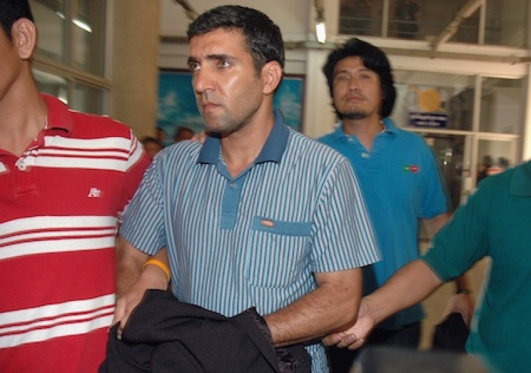 <p>Thai immigration officers escort detained Iranian Mohammad Kharzei (C) at the immigration headquarters in Bangkok on February 16, 2012.</p>