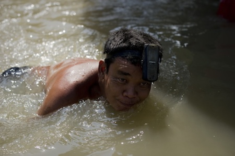 <p>A local resident swims with a mobile phone attached to his head in floodwaters after a mud and sandbag wall collapsed in Bang Bua Thong in Nonthaburi province, suburban Bangkok, on October 19, 2011. Thailand's premier urged the kingdom's rival political factions on October 19 to work together to tackle the worst floods in decades.</p>