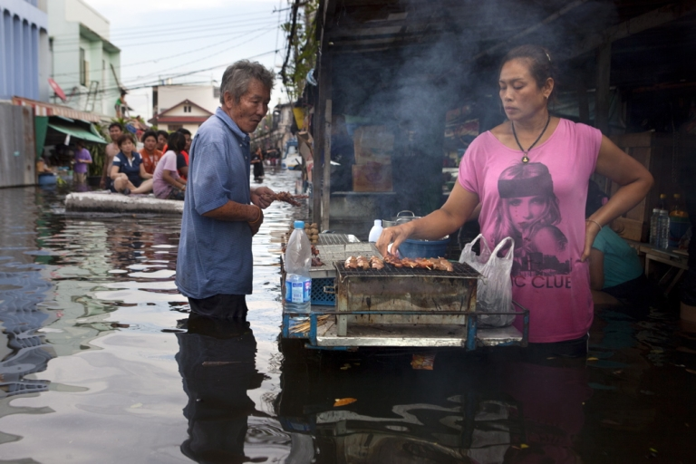 <p>A Thai woman keeps her business going cooking grilled pork in a flooded neighborhood near the Chayo Praya river as rising waters threaten parts of the capitol city October 28, 2011 in Bangkok, Thailand.</p>
