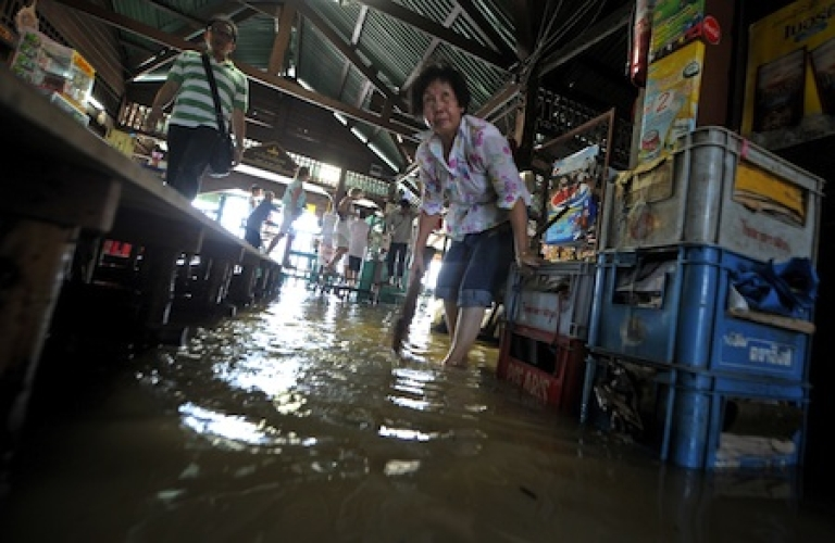 <p>A Thai woman cleans the floor of a flooded market in Bangkok on October 28, 2010.</p>