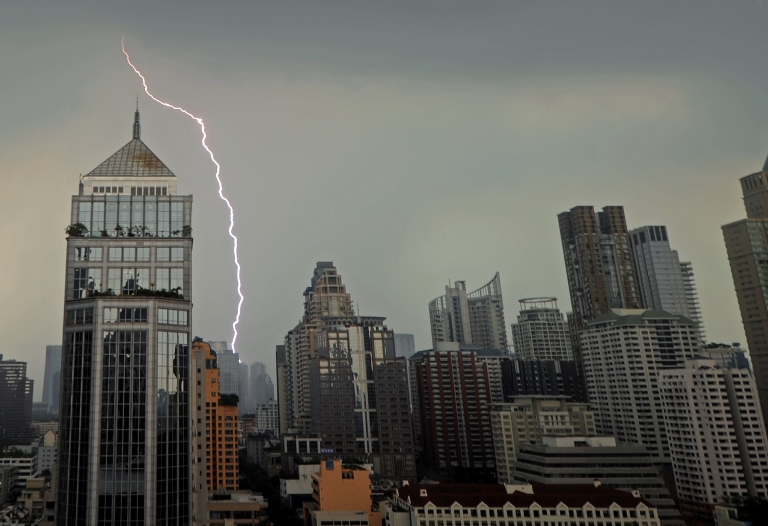 <p>Lightening streaks across the skyline during heavy rain in Bangkok on March 26, 2012.</p>