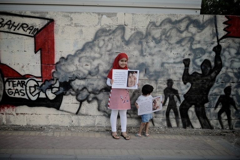 <p>Bahraini children hold up pictures of tortured democracy activists as they pose in front of graffiti depicting a scene of anti-government demonstrations in the Shiite village of Barbar on the western outskirts of the capital Manam. Shiite-led street demonstrations have turned increasingly violent, as the ruling Sunni Khalifa dynasty continues its crackdown on dissent in an effort to portray that all is well in the island kingdom ahead of the Grand Prix Formula One on Sunday.</p>