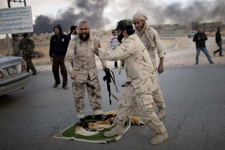 <p>Libyan National Transitional Council (NTC) fighters step on a rug bearing the image of former leader Moamer Kadhafi at the entrance to the city of Bani Walid on October 17, 2011.</p>
