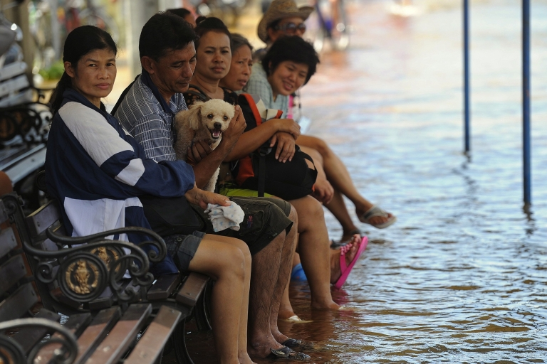 <p>Bangkok residents sit on a bench in floodwater in the Thai capital on October 26, 2011.</p>
