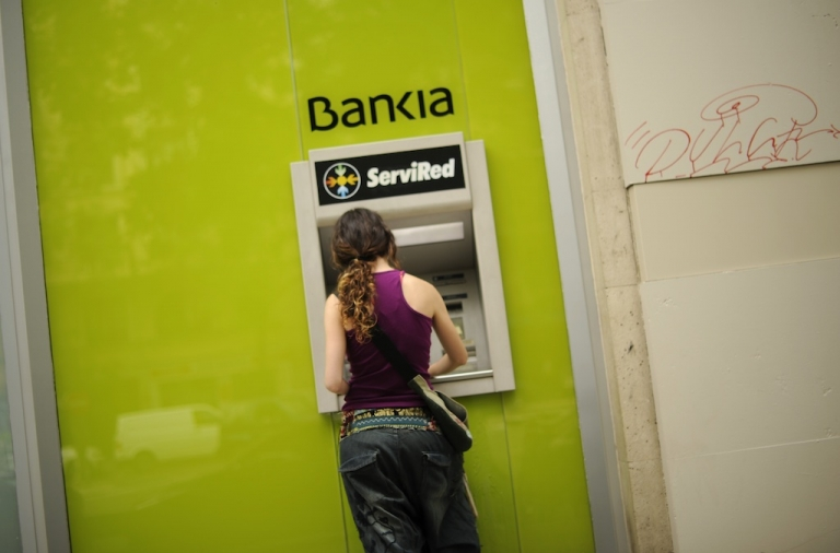 <p>A woman uses a Bankia ATM on May 17, 2012 in Madrid.</p>