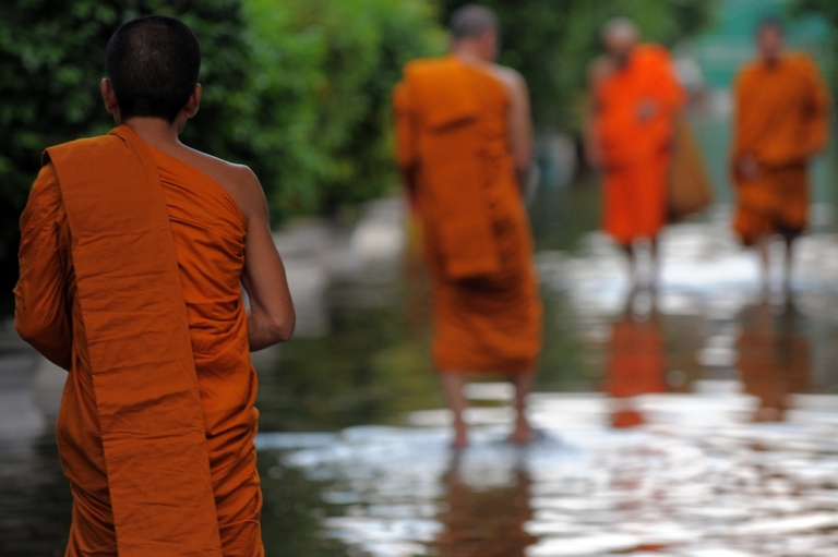 <p>Thai Buddhist monks walk through floodwaters at a pagoda in Bangkok on October 27, 2011. Thousands of Bangkok residents flocked to bus, rail and air terminals on October 27, while heavy traffic snaked out of the sprawling Thai capital in an exodus from a mass of approaching floodwater.</p>