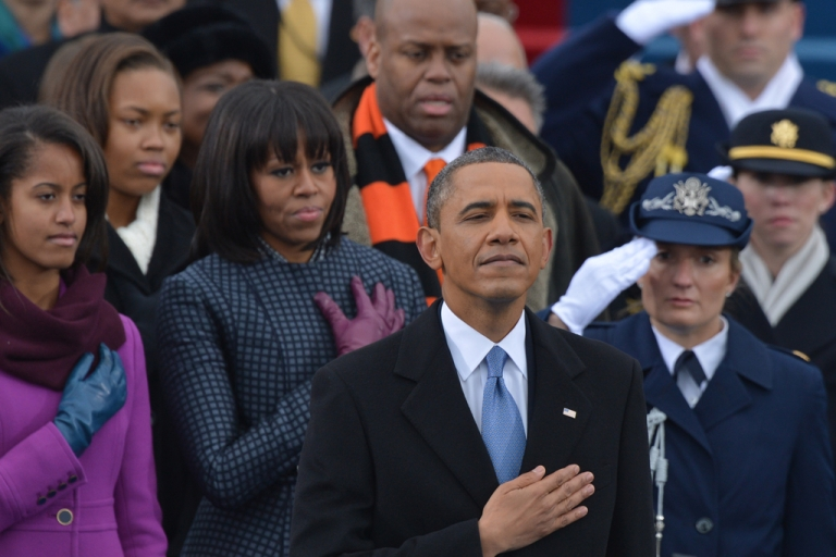 <p>US President Barack Obama, surrounded by members of his family, listens to the National Anthem during the 57th Presidential Inauguration ceremonial swearing-in at the US Capitol on Jan. 21, 2013, in Washington, D.C.</p>
