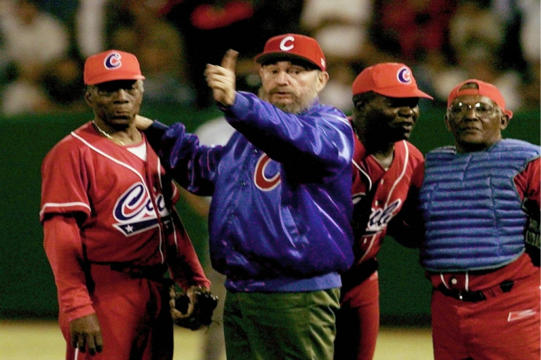 <p>Former Cuban President Fidel Castro (C) makes a call during the game between Venezuela and Cuba.</p>