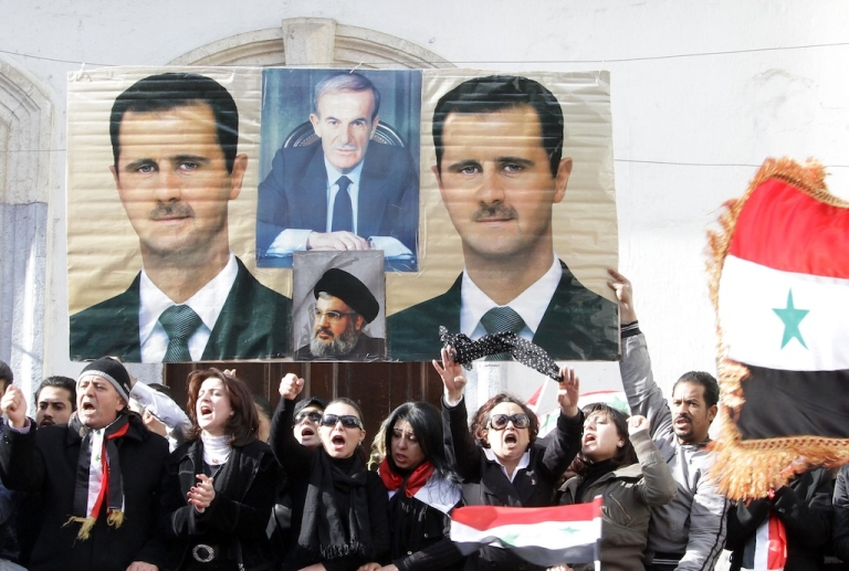 <p>Syrian mourners shout slogans as they stand under pictures of Syrian President Bashar al-Assad (L and R), late president Hafez al-Assad (top C) and Lebanon's Hezbollah chief Hassan Nasrallah during the mass funeral of 44 people killed in twin suicide bombings which targeted intelligence agency compounds at the Omayyad Mosque in Damascus on December 24, 2011.</p>