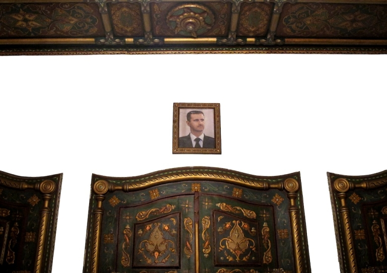 <p>A picture of Syrian President Bashar al-Assad hangs on a wall over the reception of al-Pasha hotel in Damascus on February 15, 2012. Assad has decreed to hold a referendum for a new constitution on February 26, the official SANA state news agency reported on Wednesday. AFP PHOTO/PATRICK BAZ</p>