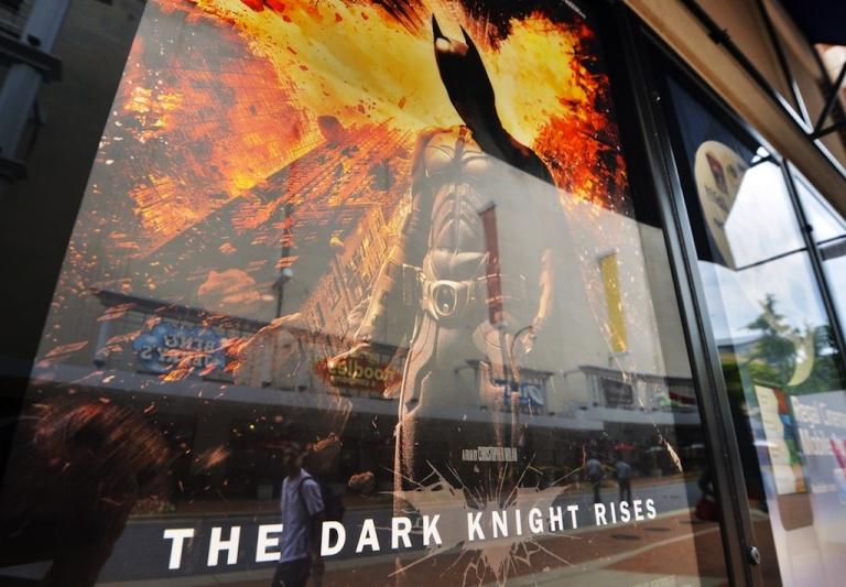 <p>People walk past a poster of the new Batman movie 'The Dark Knight Rises' outside a theater in Silver Spring, Maryland, on July 20, 2012.</p>
