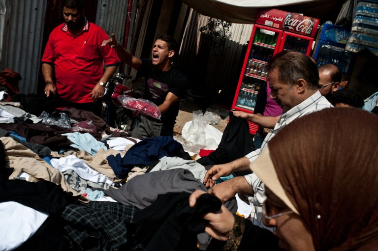 <p>A young man hawks designer clothes in a Cairo market Oct. 20.</p>
