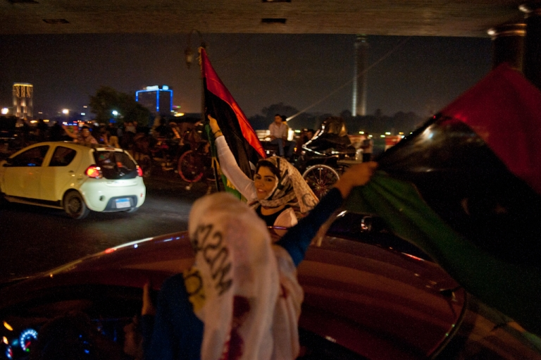 <p>Two Cairo women wave Libyan flags from a moving car after the news of Muammar Gaddafi's death spread though the streets Oct. 20.</p>