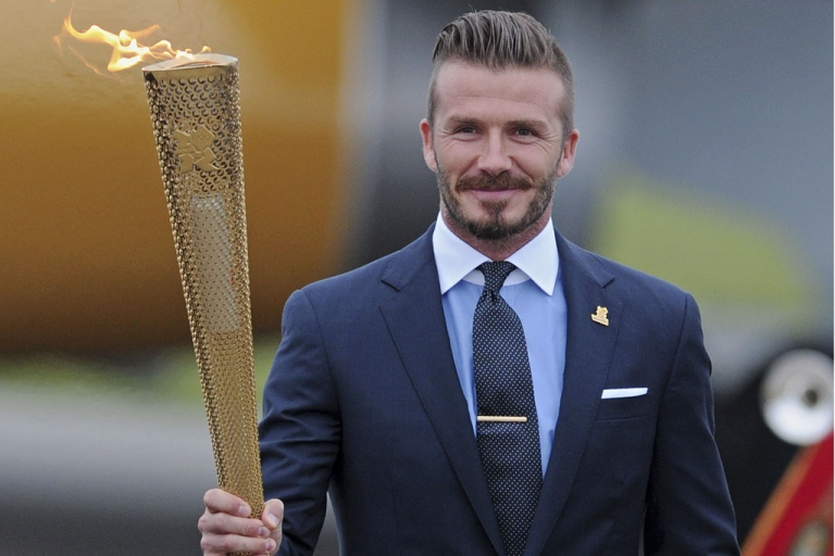 <p>David Beckham carries the Olympic torch in Cornwall, England, on May 18, 2012. The torch relay starts Saturday at Land's End, the southwest tip of England, on an 8,000-mile journey around the UK to Olympic Stadium for the opening of the Games on July 27.</p>
