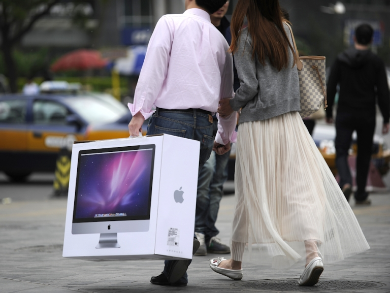 <p>A couple carries a new Mac desktop just bought from the Apple store in Beijing on May 8, 2011. Four people were taken to hospital and a glass door smashed as a near-riot broke out at Beijing's top Apple store among crowds rushing to snap up the popular iPad 2 tablet computer, state press said on May 8.</p>
