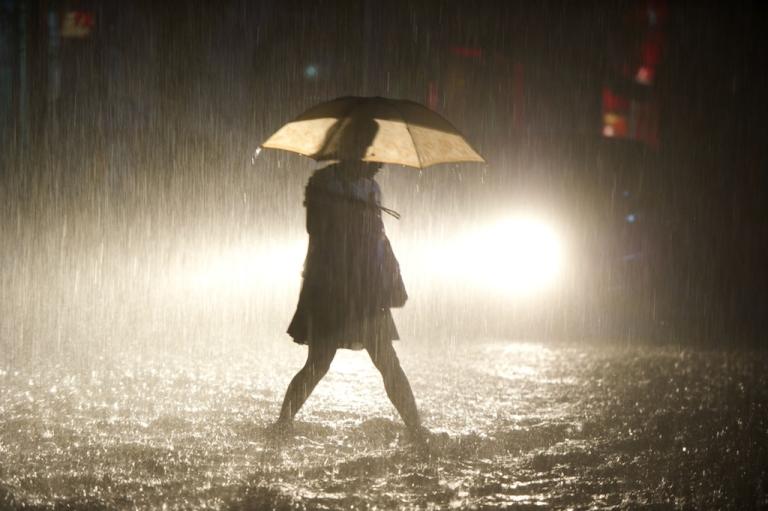 <p>A woman walks in a flooded street during heavy rain in Beijing on July 21, 2012.</p>