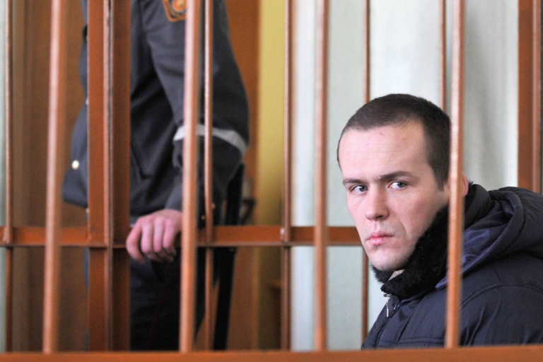 <p>Vasily Parfenkov, one of the protesters detained after December's election in Belarus, sits in the defendant cage during his trial in Minsk on Feb. 17, 2011.</p>