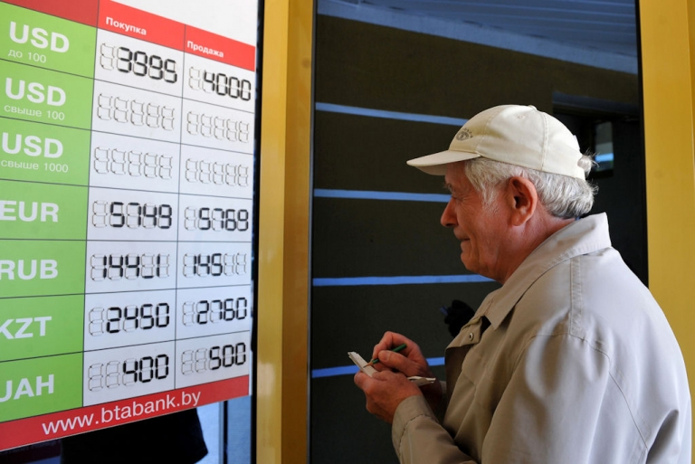 <p>An elderly man takes notes while reading foreign currency rates against the Belarus ruble outside an exchange office in Minsk, on May 11, 2011.</p>