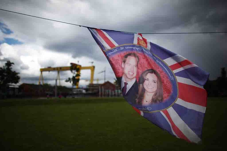 <p>A flag with images of The Duke and Duchess of Cambridge flutters in East Belfast, Northern Ireland.</p>