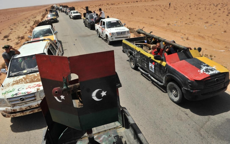 <p>Libyan rebels form a convoy, after patrolling the village of Wadi Mardum, 30 km from Bani Walid, on September 3, 2011. Rebel troops moved toward Bani Walid, a desert town southeast of the capital that is one of the last strongholds of Muammar Gaddafi.</p>