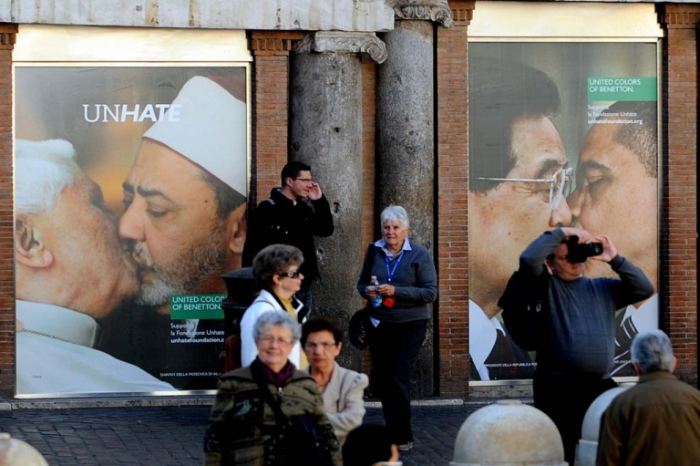 <p>People stand by a photo montage of a new ad campaign of Italian clothing company Benetton in their shop in front of the Trevi fountain in Rome on November 17, 2011.</p>