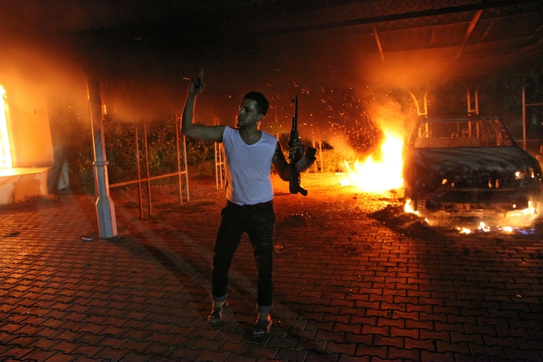 <p>An armed man waves his rifle after buildings and cars were set on fire inside the US Consulate compound in Benghazi late on Sept. 11, 2012.</p>