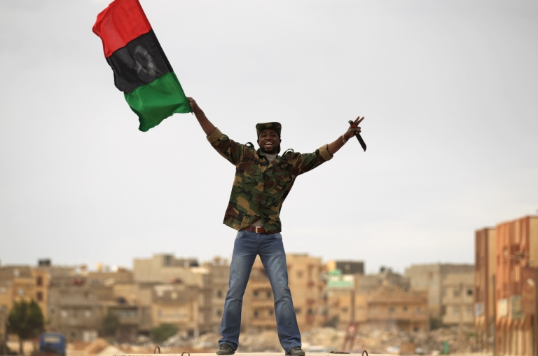 <p>A Libyan rebel fighter holds a knife as he waves the revolution flag in a street of Benghazi on March 19, 2011.</p>