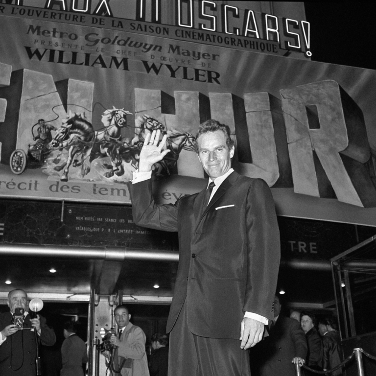 <p>US actor Charlton Heston poses in front of the poster of his last film