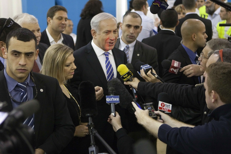<p>Israeli Prime Minister and Likud party leader Benjamin Netanyahu, accompanied by his wife Sara, speaks to the press after casting his ballot at a polling station for the party's primary vote last night in Jerusalem.</p>