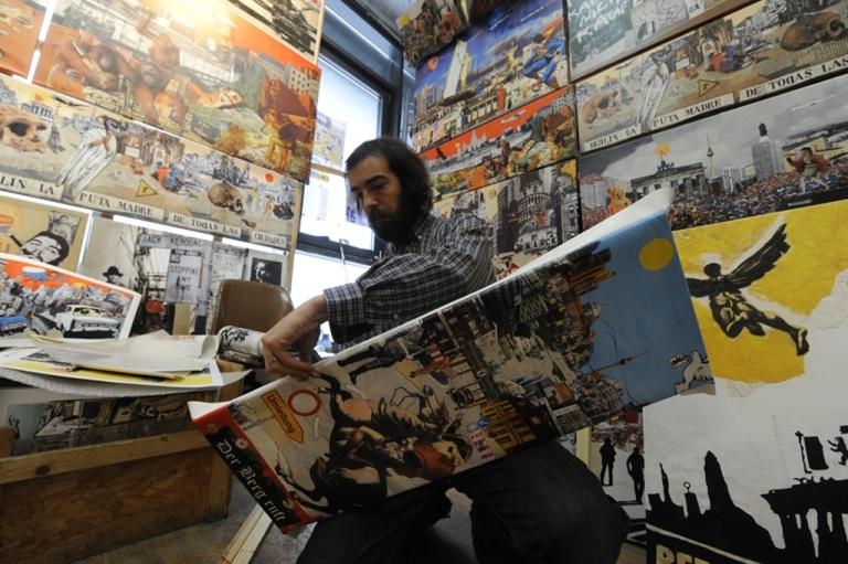<p>Artist assistant Jake Sweetman mounts prints by Dutch artist Tim Roeloffs in the Tacheles artists' colony in Berlin on Jan. 29, 2010.</p>