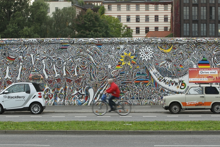 <p>Old and new: A bicycle passes a Smartcar and an East German Trabant next to a section of the Berlin Wall.</p>