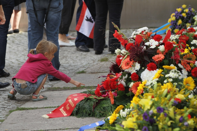 <p>Visitors look at wreaths left at a portion of the former Berlin Wall during a ceremony commemorating the 50th anniversary of its construction on August 13, 2011.</p>
