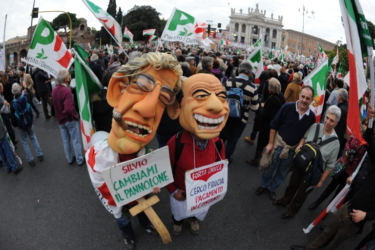 <p>Demonstrators wearing masks of Italian Prime Minister Silvio Berlusconi (R) and the leader of the Northern League, Umberto Bossi, pose with placards reading 'Silvio, change the panorama' during a demonstration 'Reconstruction.'</p>