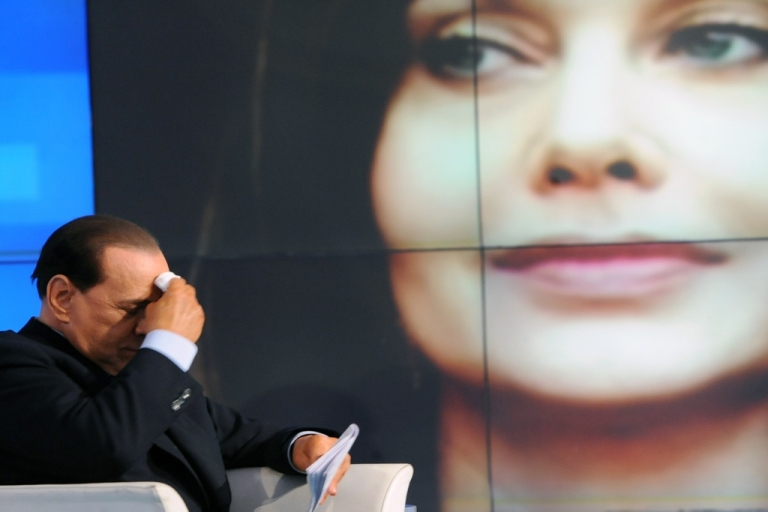 <p>Italian Prime Minister Silvio Berlusconi is seen while a portrait of his wife, Veronica Lario, is projected in the background during the recording of 'Porta a Porta,' on an Italian channel on May 5, 2009, in Rome.</p>