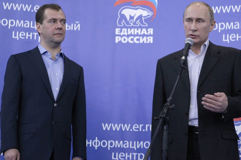 <p>Russia's President Dmitry Medvedev (L) and Prime Minister Vladimir Putin (R) speak to supporters in the United Russia ruling party's campaign staff in Moscow, on December 4, 2011.</p>