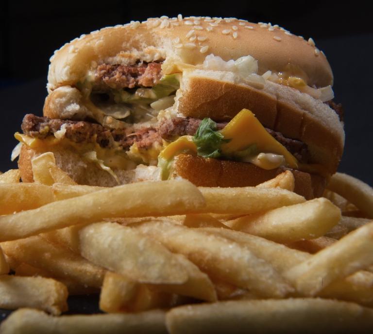 <p>A partially eaten McDonald's Big Mac and fries.</p>