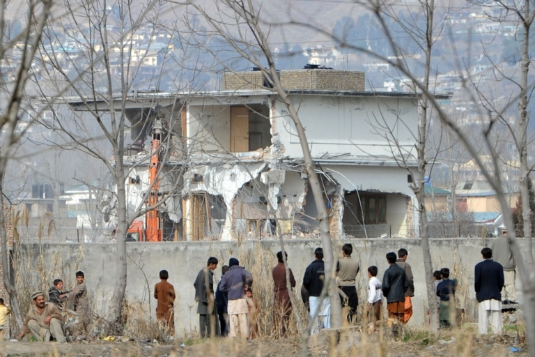 <p>Local residents watch the demolition of the compound where Osama bin Laden was slain last year in the Pakistan town of Abbottabad on Feb. 26, 2012.</p>