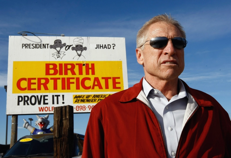 <p>Phil Wolf, owner of Wolf Automotive, stands in front of a billboard on his auto lot on November 21, 2009 in Wheat Ridge, Colorado. Wolf, a birther said he received death threats after posting the billboard.</p>