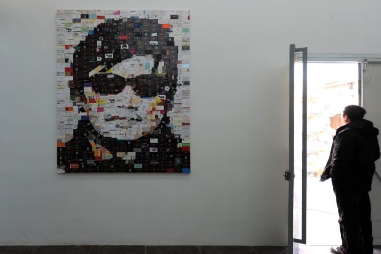 <p>A visitor stands next to a piece of art work featuring blind human rights activist Chen Guangcheng on displayed at the 798 art district in Beijing on January 9, 2012.</p>