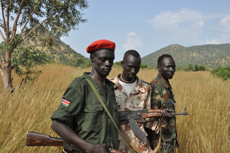 <p>SPLM-N fighters stand outside the village of Maiyas.  An Antonov bomb recently struck the village the soldiers were guarding and killed six people.</p>