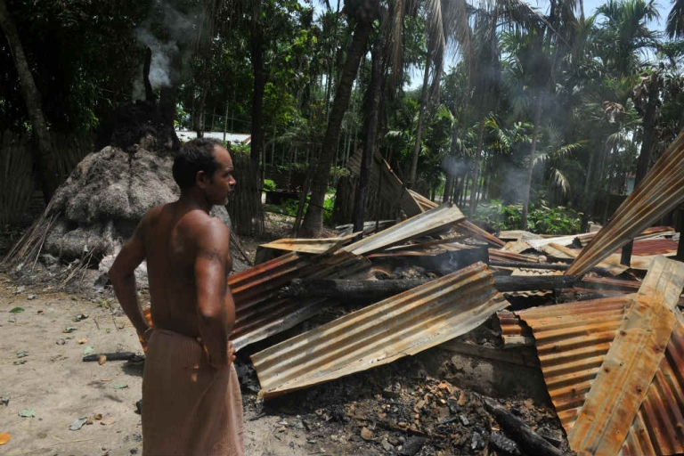 <p>An Indian villager walks amidst the debris of his burnt house in the northeastern state of Assam.</p>