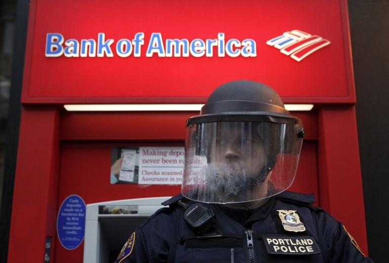 <p>A policeman in riot gear defends a Bank of America as Occupy Portland protesters march past various banks in Portland, Ore., on Nov. 17, 2011.</p>