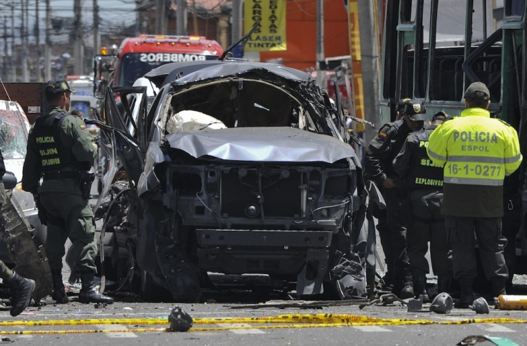 <p>Police officers inspect the wreckage of the car of former interior minister Fernando Londono on May 15, 2012 after an explosion ripped through a crowded area of Bogota's commercial district.</p>