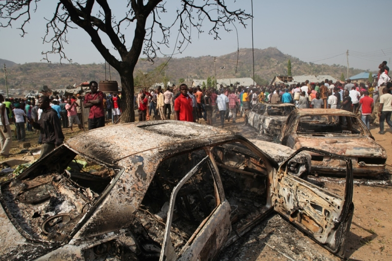 <p>People gather around burnt cars after a bomb blast in Abuja.</p>