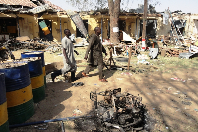<p>Two residents pass by bombed corner shops attached to police barracks in the northern Nigerian city of Kano on January 24, 2012, after multiple explosions and gun assaults by Boko Haram Islamists city killed at least 185 people.</p>